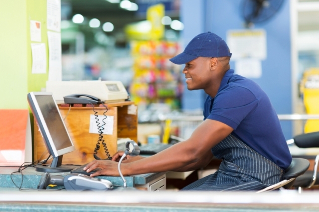 happy african male cashier working at till point in supermarket